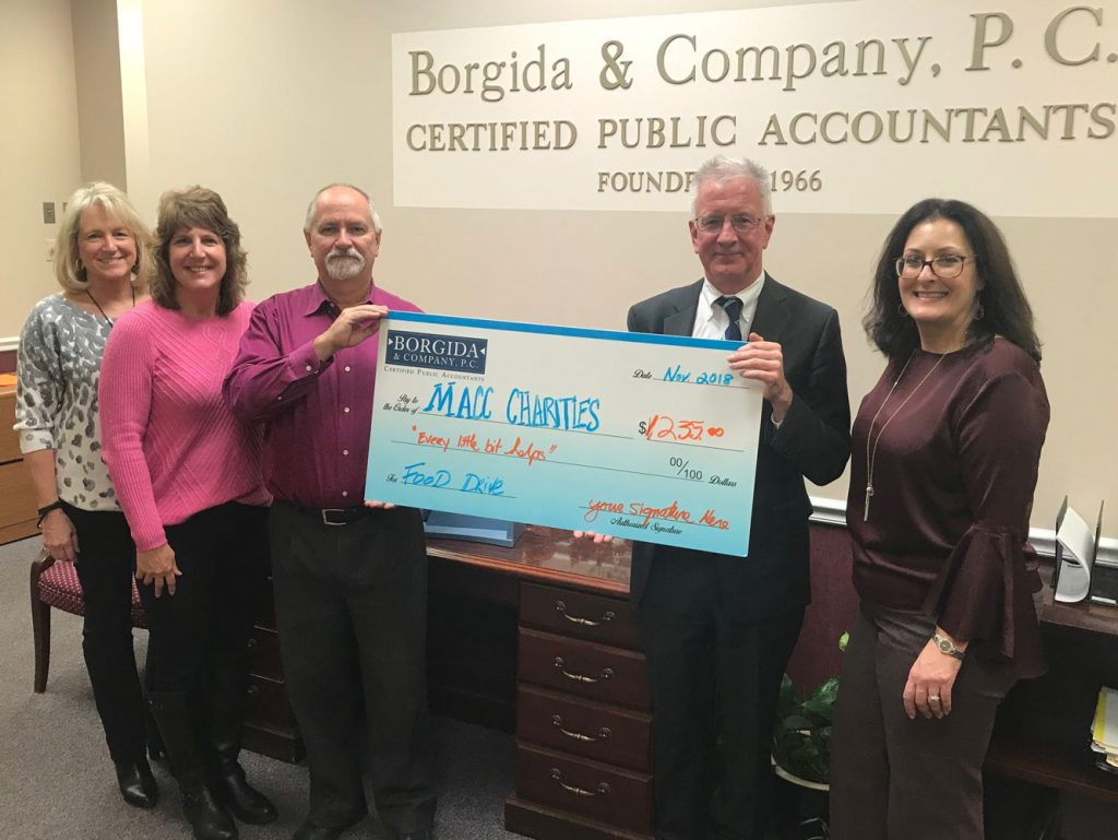 5 employees holding big check